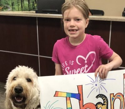 Smiling girl wearing a pink shirt holding a sign that has thank you handwritten on it while standing next to a shaggy white dog
