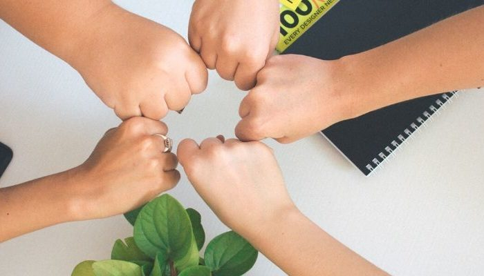 five fists touching in a circle to symbolize trust and unity
